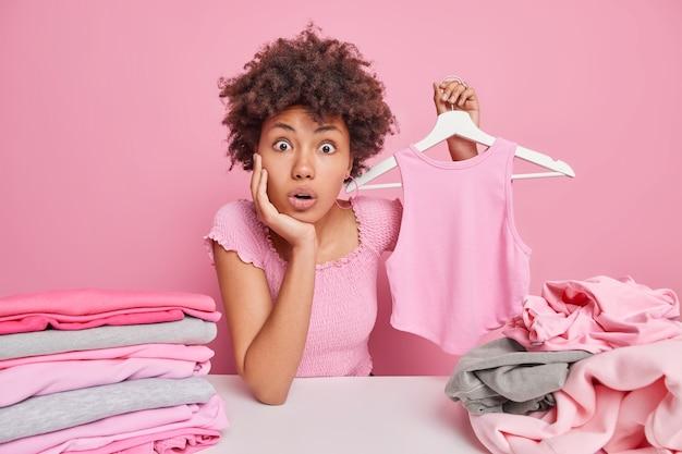 Mulher chocada e surpresa com cabelo encaracolado segura uma camiseta no cabide, dobra a roupa em casa, faz tarefas domésticas, limpa o armário senta na mesa isolada no rosa