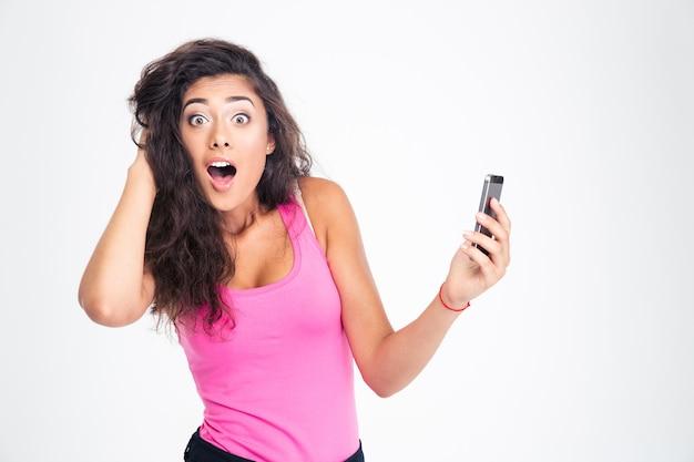 Mulher chocada em pé com smartphone