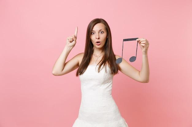 Mulher chocada em um vestido branco apontando o dedo indicador para cima segurando a nota musical escolhendo músicos da equipe ou dj