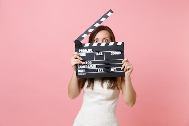 Mulher chocada em um vestido branco escondendo o rosto cobrindo o clássico filme preto fazendo claquete