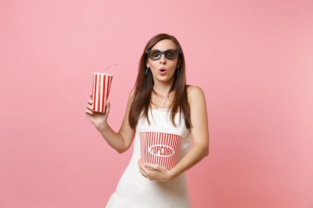 Mulher chocada em um vestido branco, óculos 3d assistindo a um filme segurando um balde de pipoca, um copo plástico de refrigerante ou cola