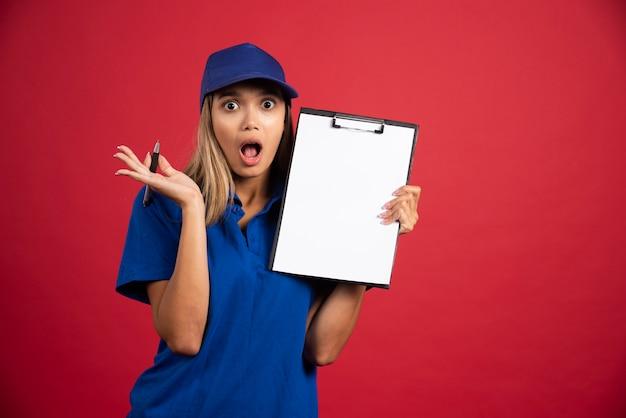 Mulher chocada em uniforme azul, segurando uma prancheta com lápis.