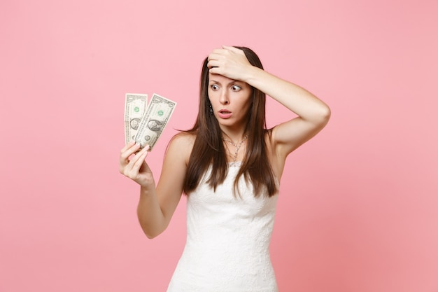 Mulher chocada em vestido branco com a mão na testa segurando notas de um dólar