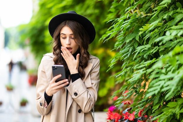 Mulher chocada encontrando notícias surpreendentes no smartphone na rua