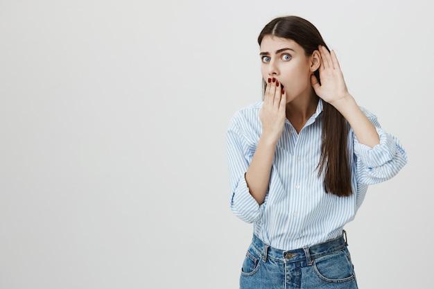 Mulher chocada escutando, tapando a boca