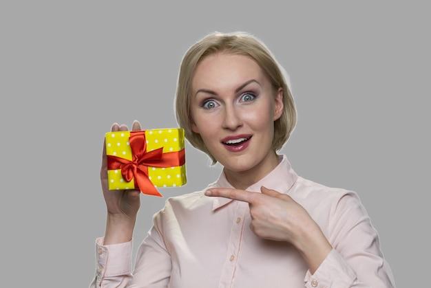 Mulher chocada feliz apontando para a caixa de presente. mulher animada segurando uma caixa peresent em fundo cinza.