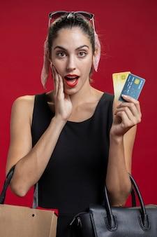 Mulher chocada, mostrando seus cartões de crédito