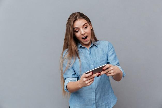 Mulher chocada na camisa que joga no telefone