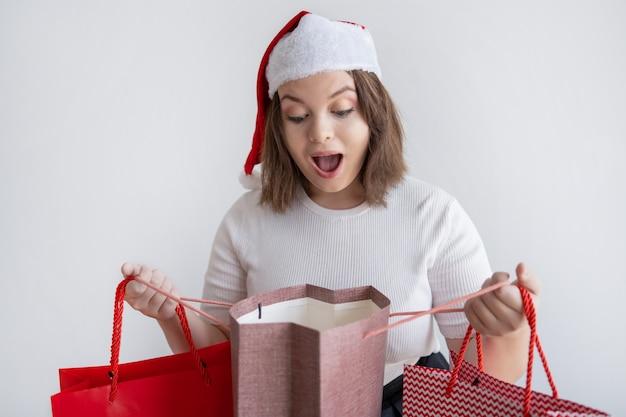 Mulher chocada no saco de abertura de chapéu de papai noel com presente de natal