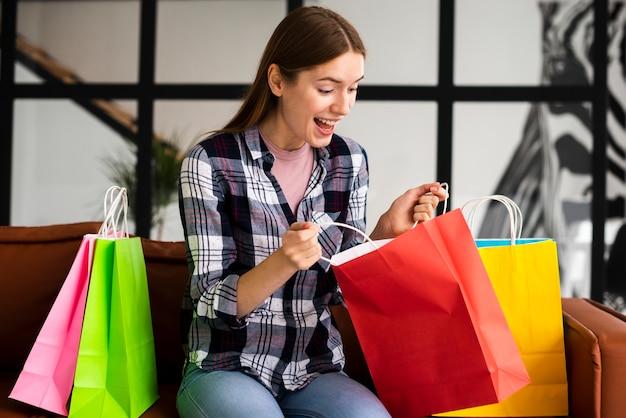 Mulher chocada olhando para dentro de sacos