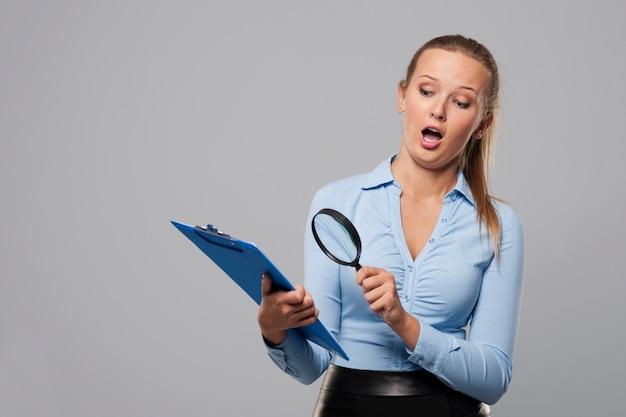 Mulher chocada olhando para documentos de escritório com lupa