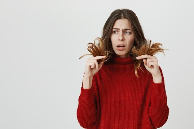 Mulher chocada olhando para pontas duplas, precisa de cabeleireiro
