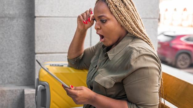 Mulher chocada olhando para seu tablet enquanto viaja