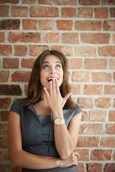Mulher chocada olhando para uma parede de tijolos