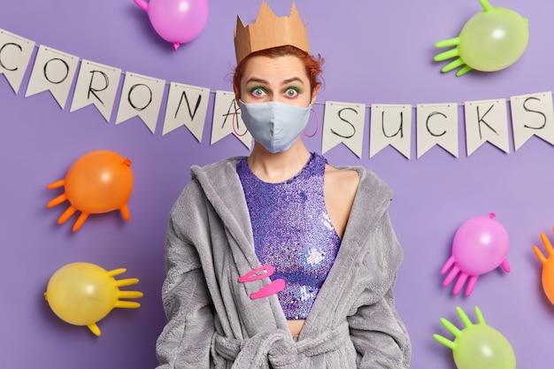 Mulher chocada se diverte em casa com auto-isolamento usa máscara protetora de papel corona e poses de vestido doméstico contra uma parede roxa com balões inflados e guirlandas
