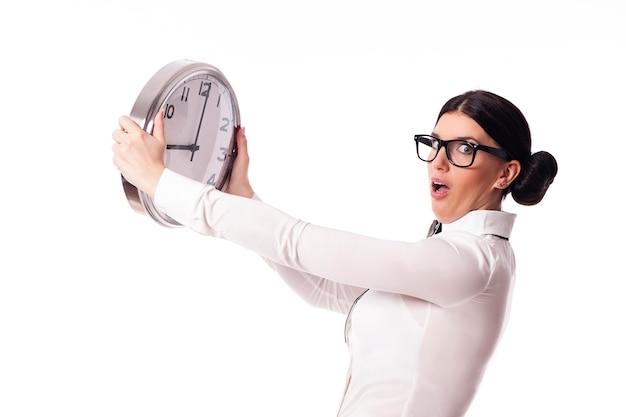 Mulher chocada segurando um relógio de escritório