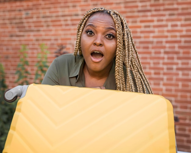 Mulher chocada segurando uma bagagem amarela