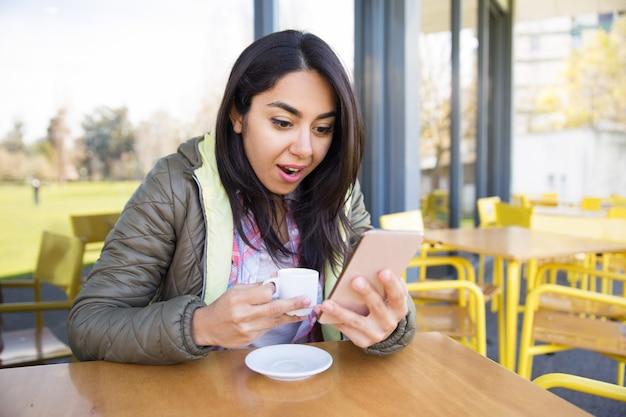 Mulher chocada usando smartphone e tomando café no café