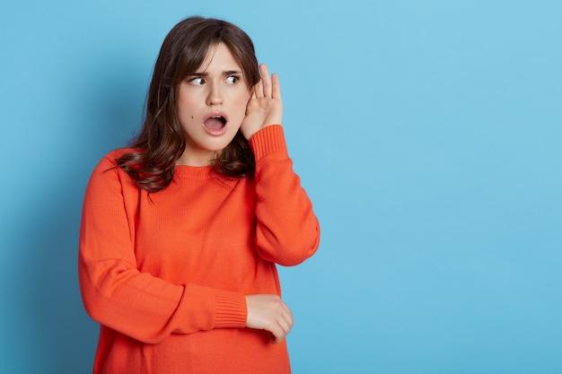 Mulher chocada, vestindo um suéter laranja casual posando com a palma da mão perto da orelha, tentando ouvir algo, isolado sobre a parede azul.
