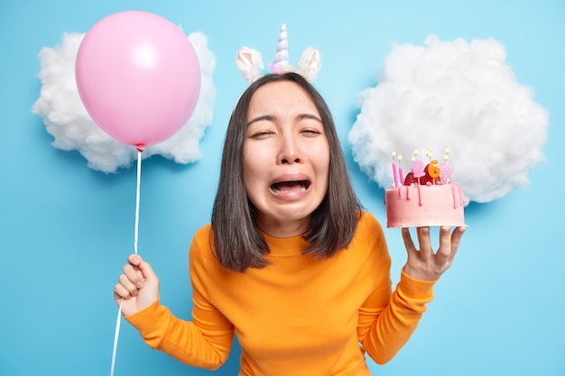 Mulher chora de desespero segurando balão inflado e sobremesa saborosa com humor infeliz no aniversário