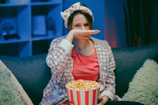 Mulher chora enquanto assiste a um filme muito emocionante com pipoca à noite.