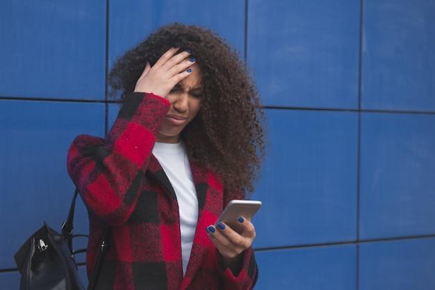 Mulher chorando com um telefone em um fundo escuro
