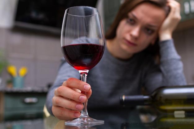 Mulher chorando, deprimida e divorciada, sentada sozinha na cozinha de casa e bebendo um copo de vinho tinto por causa de problemas no trabalho e problemas nos relacionamentos. problemas sociais e da vida