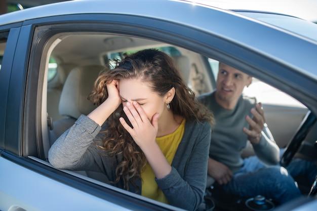 Mulher chorando e homem bravo, sentado em um carro