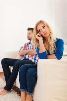 Mulher chorando sentada com o namorado ao fundo
