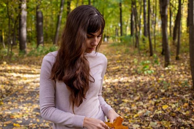 Mulher chorando triste no parque. jovem mulher bonita com folha de outono no parque outono, sob o sol brilha