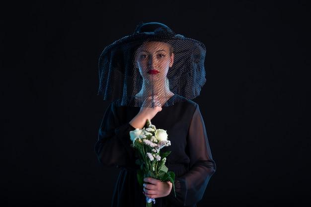 Mulher chorando vestida de preto com flores em um funeral de tristeza negra