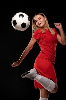Mulher chutando bola com o pé