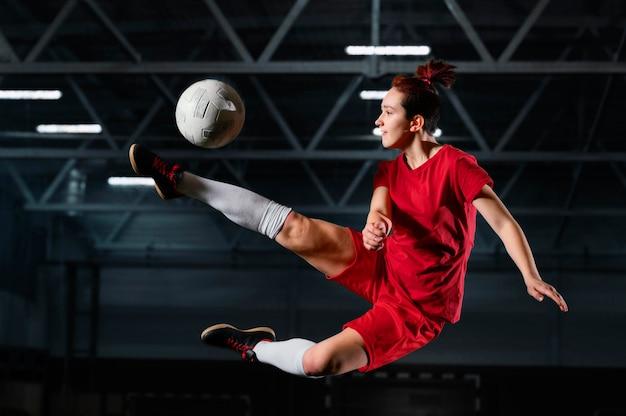 Mulher chutando bola de futebol