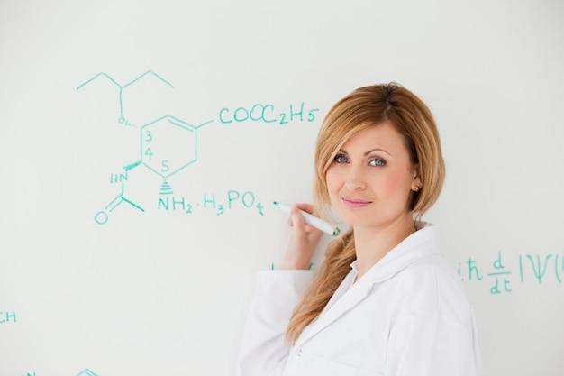 Mulher cientifica olhando a câmera ao escrever uma fórmula em um quadro branco