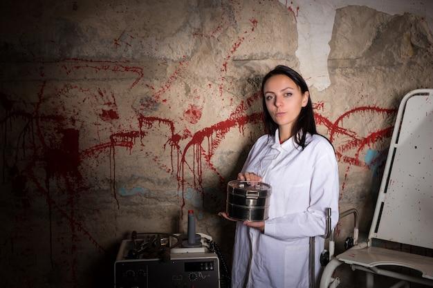 Mulher cientista segurando uma caixa de alumínio em frente a uma parede respingada de sangue, conceito de halloween