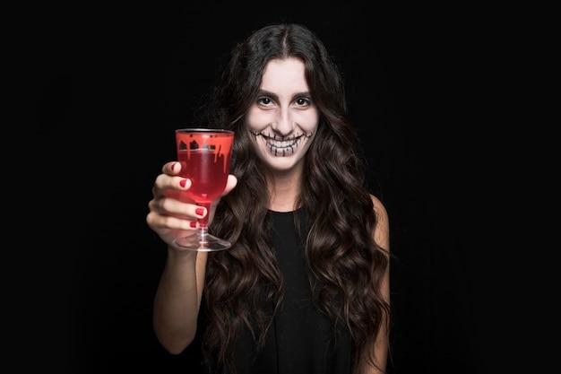 Mulher cinza mostrando o vidro com líquido vermelho