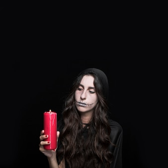 Mulher cinzenta olhando a vela acesa
