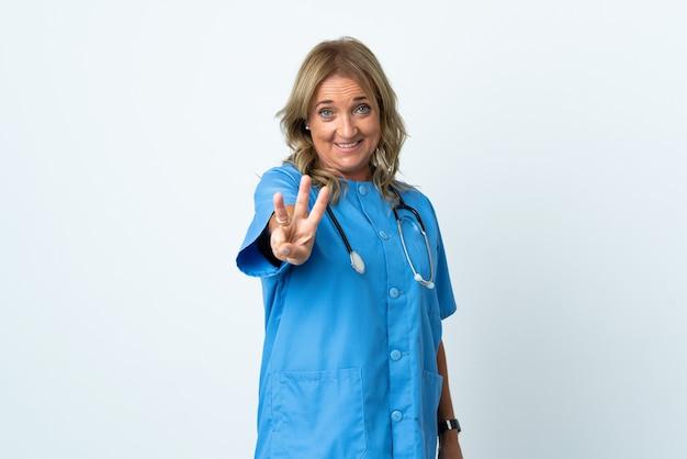 Mulher cirurgiã de meia-idade feliz em uma parede isolada contando três com os dedos