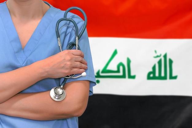 Mulher cirurgiã ou médica com estetoscópio contra a bandeira do iraque