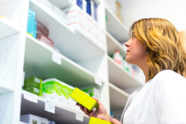 Mulher cliente na farmácia olhando os medicamentos na prateleira
