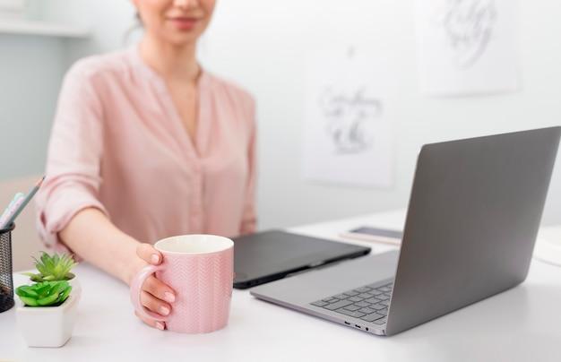 Mulher close-up, bebendo café, enquanto trabalhava