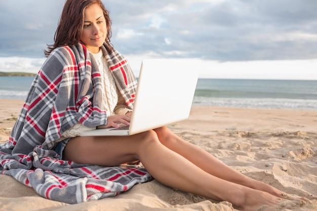 Mulher coberta com manta usando laptop na praia