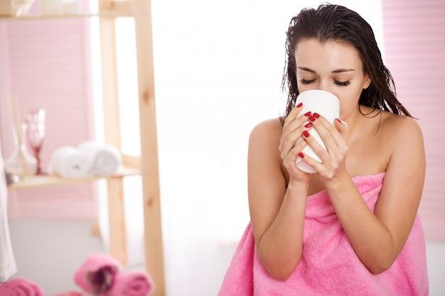 Mulher coberta com toalha rosa bebe chá após tratamento de beleza