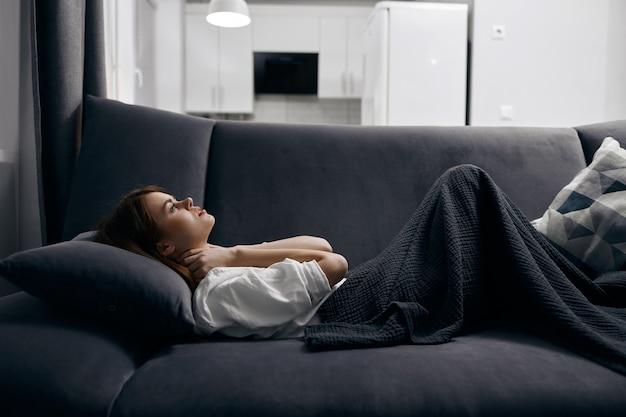 Mulher coberta com um cobertor está deitada no sofá.