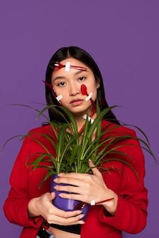 Mulher coberta de colheres e garfos de plástico enquanto segura uma planta