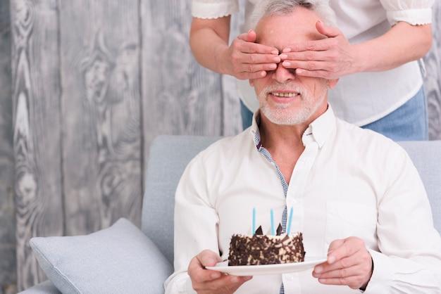 Mulher, cobertura, dela, marido's, olhos, segurando, bolo aniversário, em, mão