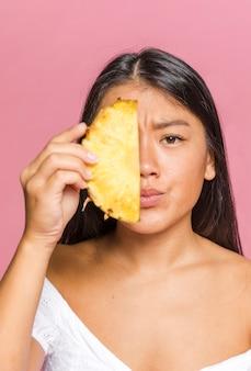 Mulher, cobertura, dela, rosto, com, cortado, abacaxi