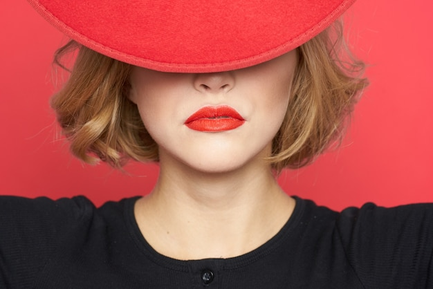 Mulher cobre os olhos com chapéu vermelho