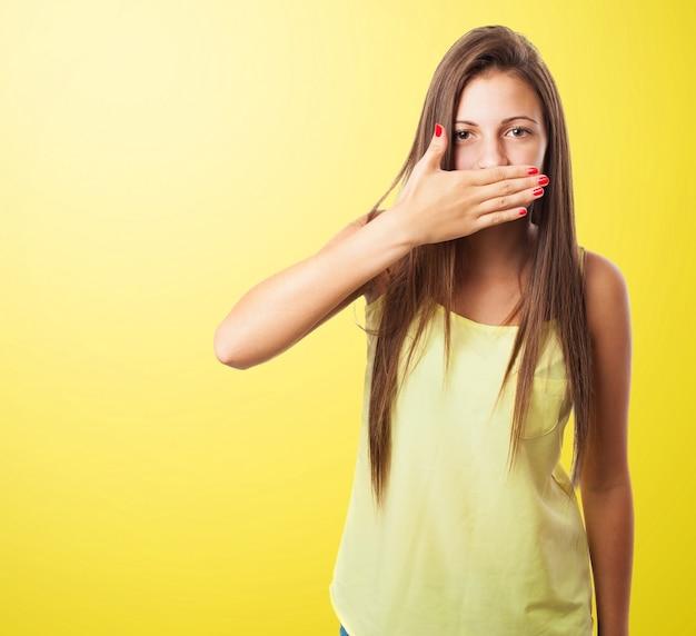Mulher cobrindo a boca em um fundo amarelo