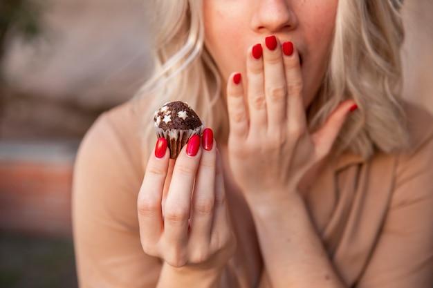 Mulher cobrindo a boca enquanto segura o cupcake